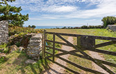 Opposite Kittiwake's front door is a five bar gate looking over farm fields to the sea